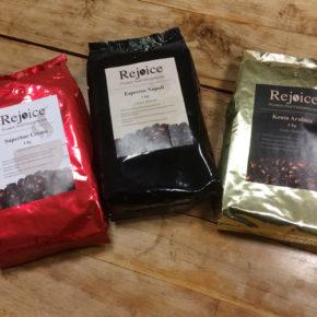3 Kaffeeverpackungen (rot, schwarz, gold) mit Aufkleber